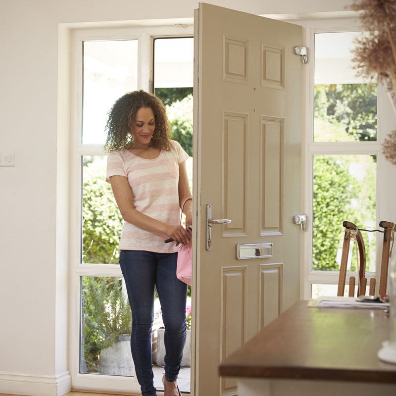 Photo of woman opening front door of her new house which she bought as a first time buyer