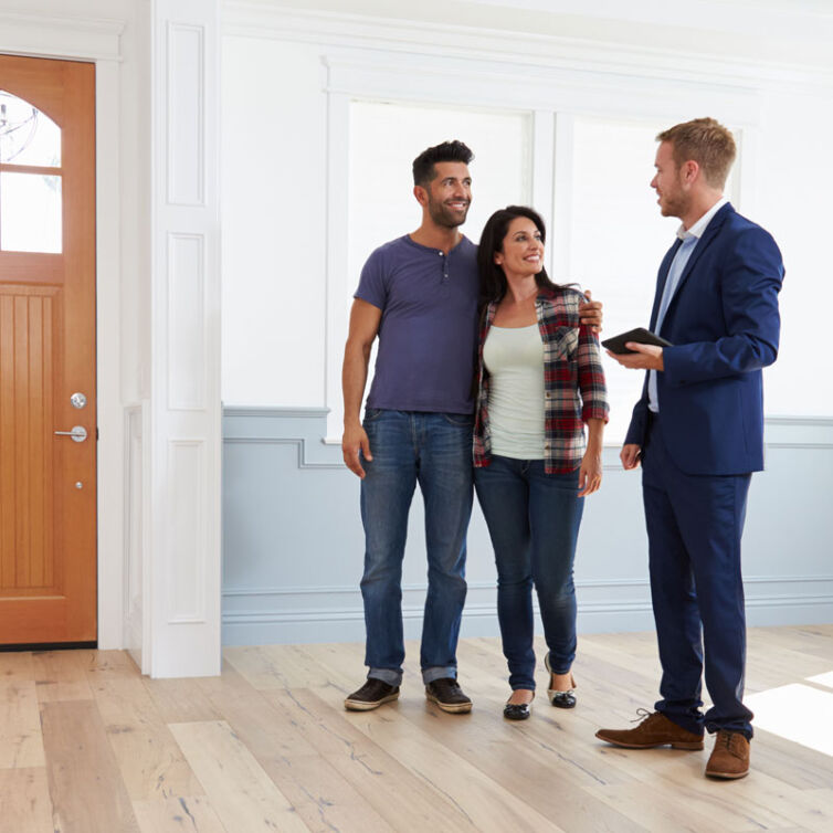 Photo of happy couple with sales man buying their new Help to Buy home