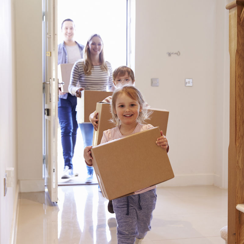 Photo of young family moving into their new house after getting their new mortagage with boxes in their arms