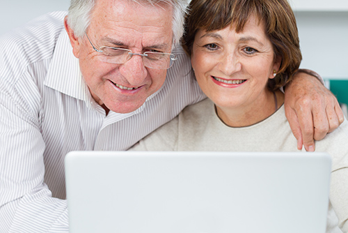 Couple looking at computer while they search for equity release information that is provided by Acclaimed Mortgage Consultancy